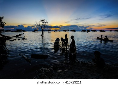 Amazing silhouette of seagypsy boy during sunset in a Mabul Island, Sabah, Malaysia