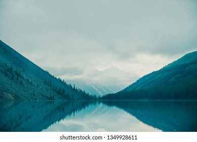 Amazing silhouettes of mountains and low clouds reflected on mountain lake. Beautiful ripples on water mirror. Cloudy sky in highlands. Atmospheric ghostly landscape. Wonderful mystic mountainscape.