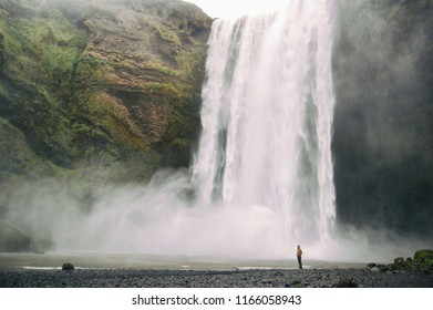 Amazing Skogafoss waterfall landscape with a man standing alone
