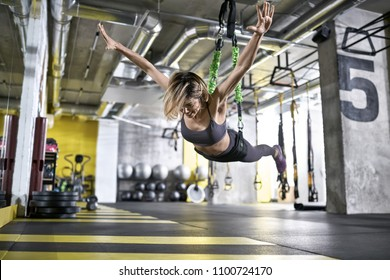 Amazing smiling girl is training with goflo-trainer in the gym. She is hanging in the air with outstretched arms. Woman wears a gray top and pants, violet sneakers. Horizontal.