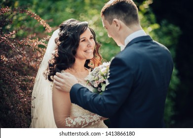 Amazing smiling wedding couple Beautiful bride and groom embracing and kissing on their wedding day.