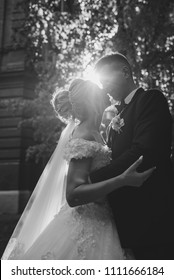 Amazing smiling wedding couple. Pretty bride and stylish groom. Wedding photo outdoor. White dress and black suit. Kisses of a smile.
