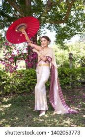Amazing smiling wedding. Romantic Asian Bride Thailand  Culture. Beauty bride wedding dress Thailand  Culture With a bouquet walks in the autumn park, yellow leaves.Laos bride.
