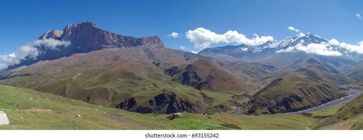 Amazing summer landscape in the Caucasus Mountains. Scenic view of green meadows, valley of the river and snow-covered mountain. Red rock Erydag - popular place of mountaineering. Russia, Dagestan