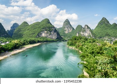 Amazing summer sunny landscape at Yangshuo County of Guilin, China. Beautiful view of karst mountains and the Li River (Lijiang River) with azure water. Wonderful green hills on blue sky background.