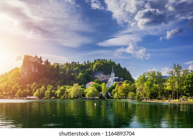 Amazing sunny scenery of Bled castle and St. Martin's Church and Bled town with reflection in the lake and the Julian Alps on background. Bled Lake, Slovenia.