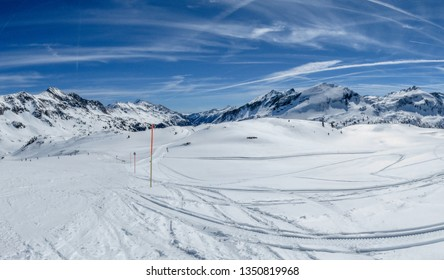 Amazing sunny winter day on ski slopes. Just a perfect conditions for skiing. Mountains peaks, blue skies, almost no clouds, warm and quiet. Ideal for a weekend getaway and adventure.