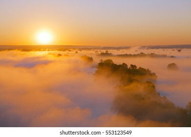 Amazing sunrise over hills with trees covered by fog. Bright orange mood