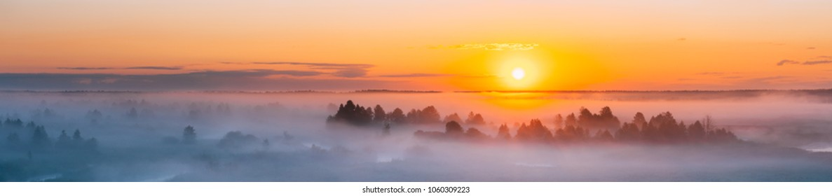 Amazing Sunrise Over Misty Landscape. Scenic View Of Foggy Morning Sky With Rising Sun Above Misty Forest. Middle Summer Nature Of Europe. Panorama, Panoramic Shot.