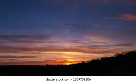 Amazing sunrise in rural scene. Dramatic sky with sunbeam and stratus clouds over the silhouette of hill on the horizon.