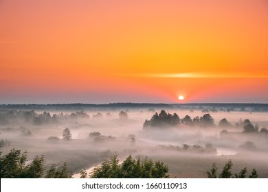 Amazing Sunrise Sunset Over Misty Landscape. Scenic View Of Foggy Morning Sky With Rising Sun Above Misty Forest And River. Early Summer Nature Of Eastern Europe.