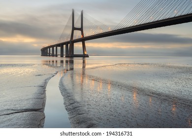 Amazing sunrise in the Vasco da Gama Bridge in Lisbon, in a morning fog. Landscape of one of the main attractions of Portugal, one of the longest bridges in the world.