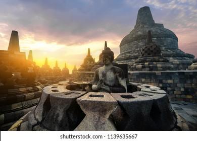 Amazing sunrise view of meditating Buddha statue and stone stupas against shining sun on background. Ancient Borobudur Buddhist temple. Great religious architecture. Magelang, Central Java, Indonesia