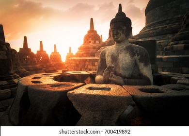 Amazing sunrise view of meditating Buddha statue and stone stupas against shining sun on background. Ancient Borobudur Buddhist temple. Great religious architecture. Magelang, Central Java, Indonesia