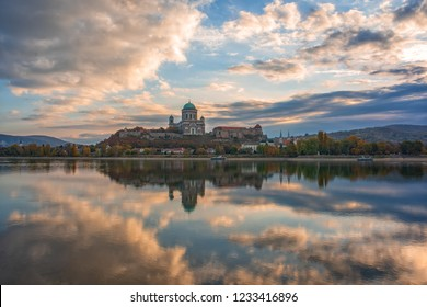 Amazing sunrise view over Danube river, beautiful reflections of morning clouds mirrored in water, Esztergom, Hungary. Basilica of the Blessed Virgin Mary and royal castle. Travel destination scene