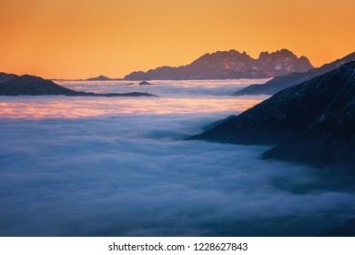 Amazing sunset in Alps mountains over cloud and mountain ridge in sunlight, Hohe Tauern national park, Carinthia, Austria