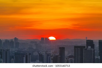 Amazing sunset in city, half of sun sink in the mountains. Fiery orange sunset sky. Beautiful sky background.