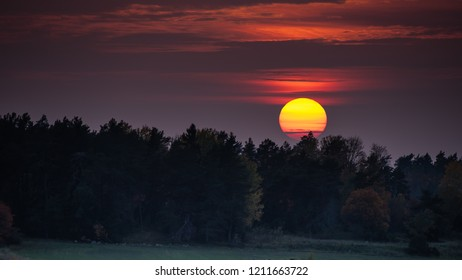 Amazing sunset at an hazy evening behind the forest in october, Uppland, Sweden