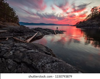 Amazing sunset with mans silhouette along water in the sunshine coast, British Columbia, Canada.