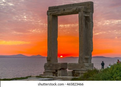 Amazing sunset in Naxos, Cyclades, Greece. The incredible gate (Portara) of Apollo in the foreground.