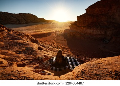 Amazing Sunset on Desert Wadi Rum, Girl is sitting on carpet and she is resting. Best view ever. Landscape of Red Desert Wadi Rum in Jordan. Sunny day, rock formations and endless horizon.