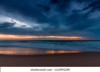 Amazing sunset on the ocean. View of dramatic cloudy sky and reflection of the sunlight on water. Atlantic coast  near Lisbon. Portugal.