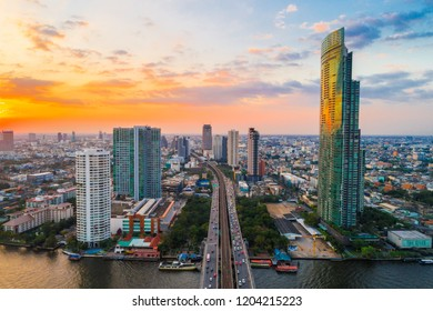 Amazing Sunset on river over the city building with transport road aerial view, Bangkok Thailand