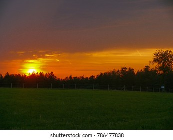 Amazing sunset over a dark green countryside landscape of rolling hills with sun beams piercing sky and lighting hillside