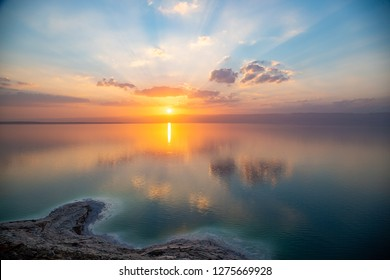 Amazing sunset over Dead sea, view from Jordan to Israel and Mountains of Judea. Madaba governorate and Karak governorate. Reflection of sun, skies and clouds. Salty beach, salt on Dead sea coast.