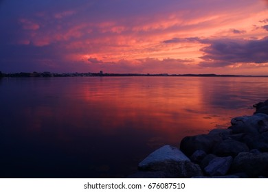 Amazing sunset over the lake.Landscape with a beautiful dramatic sunset sky after evening storm reflects in lake Mendota in the city of Madison Tenney Park,Wisconsin,USA.Long exposure horizontal shot.