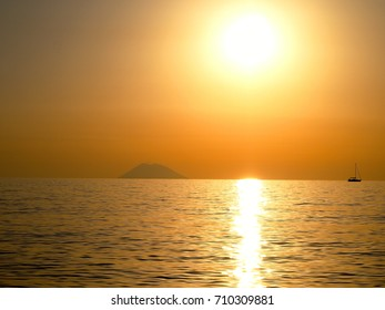 Amazing sunset over the sea with sailboat and volcano Stromboli in the background