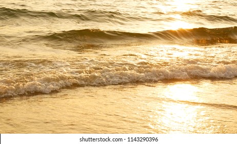 amazing sunset over the tropical beach. ocean beach waves on beach at sunset time , sunlight reflect on water surface. beautiful evening nature sea background.