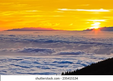 Amazing sunset at the peak of volcano Teide, Tenerife, Canary Islands, Spain. Aerial view over clouds above ocean water with last sunshine .