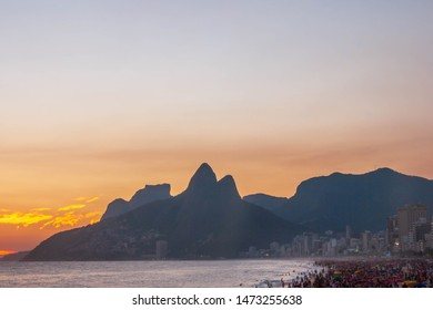 Amazing sunset at Rio de Janeiro litoral seen from Arpoador rock depicting Ipanema beach with a crowd on the sand and the silhouette of the mountains