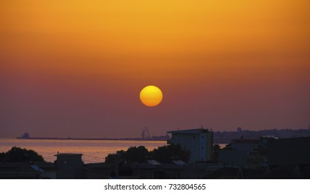 Amazing sunset scenery, bright sun dusk above sea port and silhouette of greek city at the background of purple, orange and yellow sunset sky. View from Amoudara, Heraklion, Crete island, South Greece