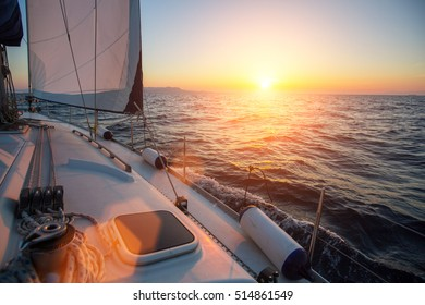 Amazing sunset at sea shot of a luxery yacht boat. Sailing in the wind through the waves.