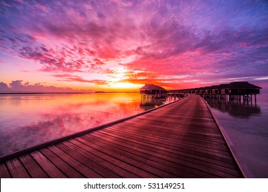 Amazing sunset sky and reflection on calm sea, Maldives beach landscape of luxury over water bungalows. Exotic scenery of summer vacation and holiday background