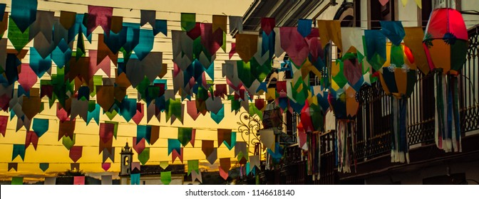 "Amazing sunset view with balloons and colorful paper flags in first plan. June party in Brazil, also ""festas juninas"" or ""São João"" in portuguese."