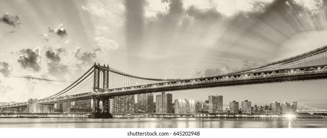 Amazing sunset view of Manhattan Bridge with East River reflections - New York City.