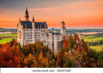Amazing sunset view on Neuschwanstein Castle with colorful sky and autumn trees. Bavaria, Germany.