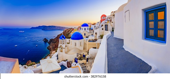 Amazing sunset view with white houses in Oia village on Santorini island in Greece.