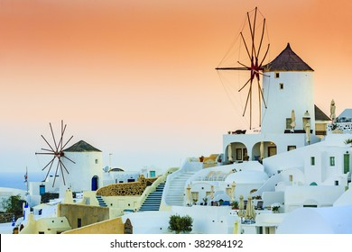 Amazing sunset view of windmills in Oia village on Santorini island in Greece.