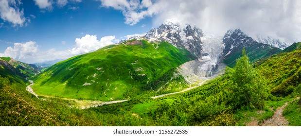 Amazing Svaneti mountain landscape on sunny summer day. Mount Tetnuldi and glacier Lardaad, green grassy hills, mountain river in Georgia. Blue sky and clouds over mountains trek. Hiking in Adishi