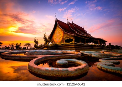 Amazing Temple Sirindhorn Wararam Phuproud in Ubon Ratchathani Province at twilight time,Thailand.Thai temple with grain and select white balance.Night sky effect for Long exposure fluorescent light.