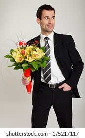 Amazing thoughtful man at suit with bouquet of orchids for Valentine.