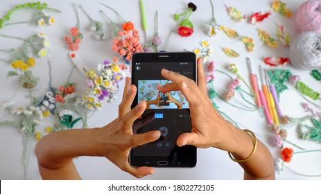 Extraordinaire vue de dessus prise de vue du moment du crochet fait à la main produit de femme photographe via un minuteur installé à partir d'une tablette, une tablette à deux mains et la photo à partir d'une fleur colorée sur fond blanc
