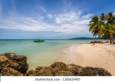 Amazing tropical beach in Caribe, boat with tourists, palm trees, white sand beach - Trinidad and Tobago