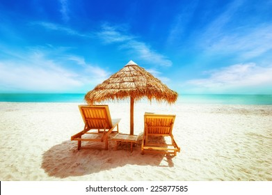 Amazing  tropical beach landscape with thatch umbrella and chairs for relaxation on sand. Travel background and destinations