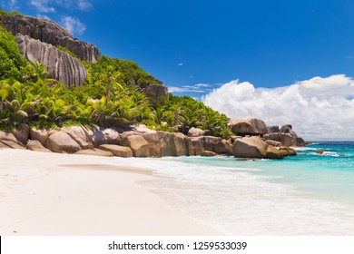 Amazing tropical beach with palm trees and granite boulders on Grande Soeur, Seychelles