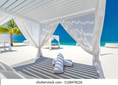 Amazing tropical beach scene with white canopy and curtain for luxury summer relaxation concept. Blue sky with white sand for sunny beach landscape background and summer vacation or holiday design